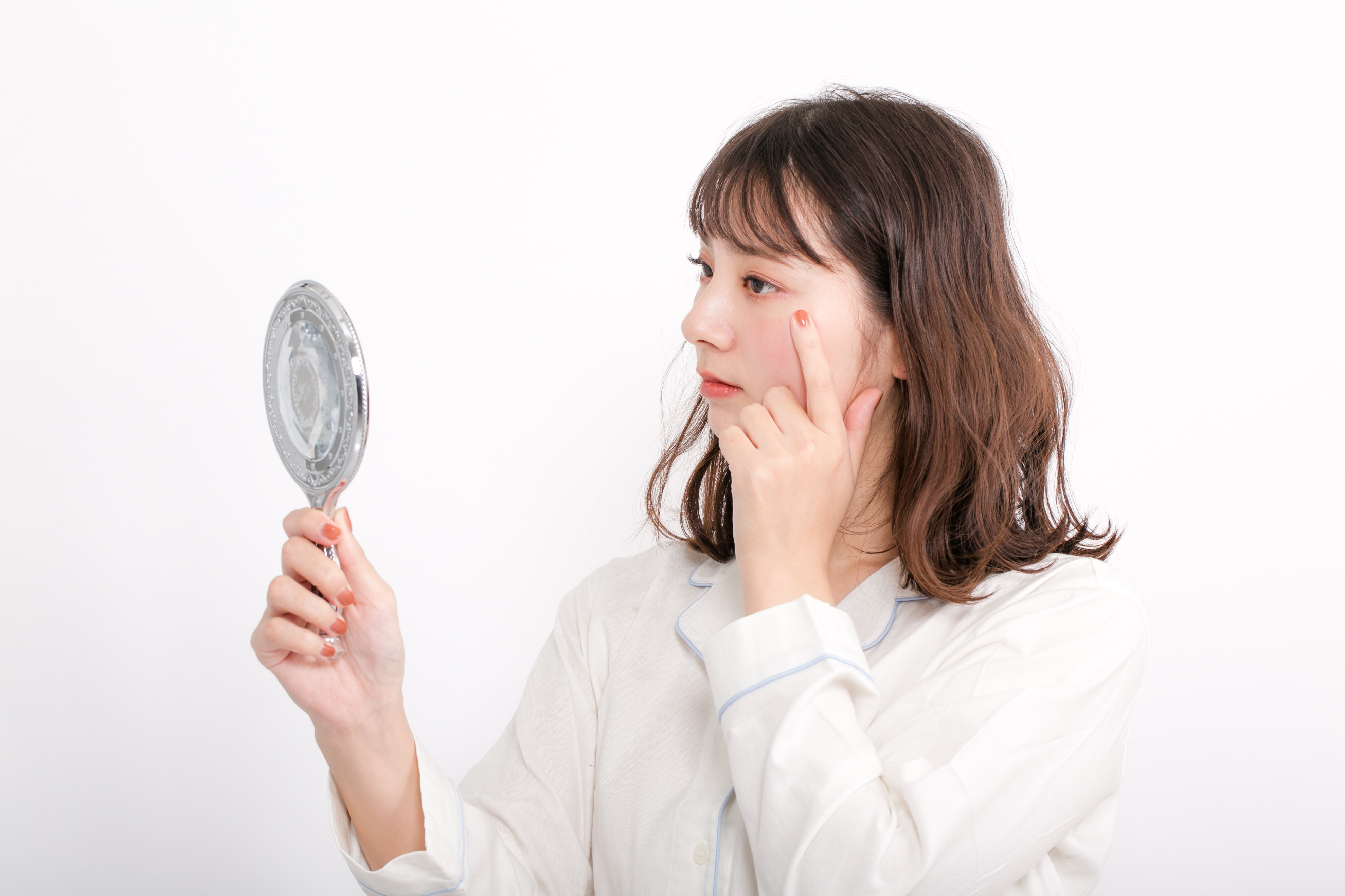 マツエクをして鏡を見ている女性